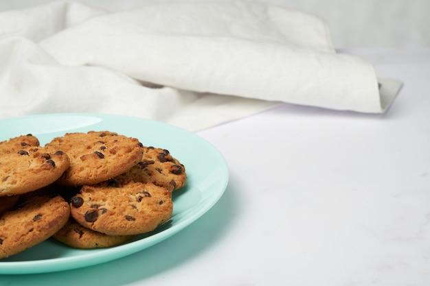 Schokoladenkekse auf einem hellblauen teller mit einem weißen tuch hinten