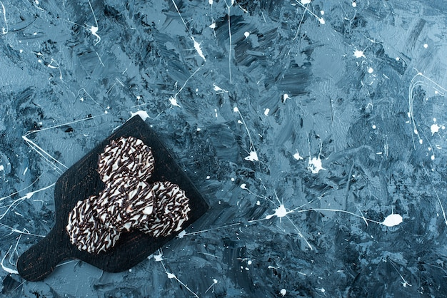 Schokoladenkekse auf einem schneidebrett auf dem blauen tisch.