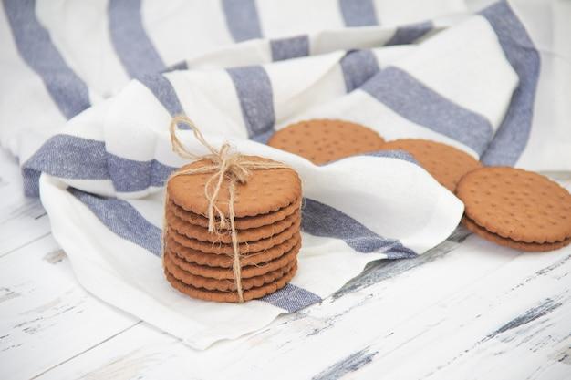 Schokoladenkekse auf heller serviette auf weißem holztisch.
