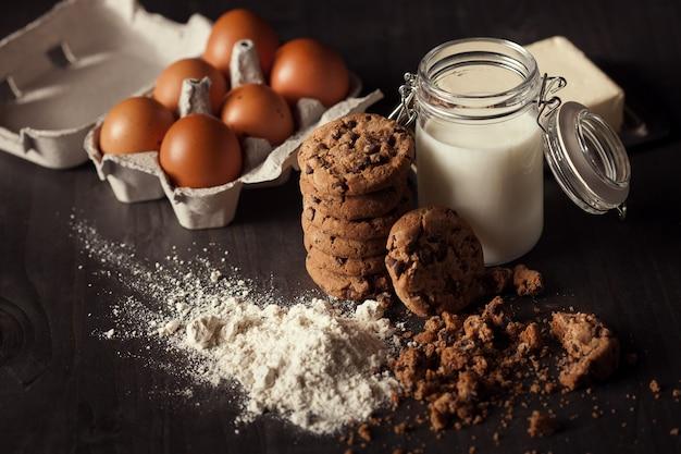 Schokoladenkekse auf rustikalem holztisch mit flasche milch, weißmehl, frischen eiern, butter und krümel. gesunder nachtisch.