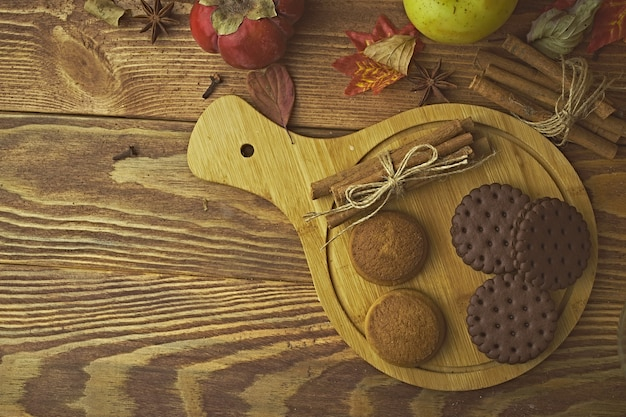 Schokoladenkekse auf tablett zimtstangen kaki und äpfel im hintergrund herbsternte auf ...