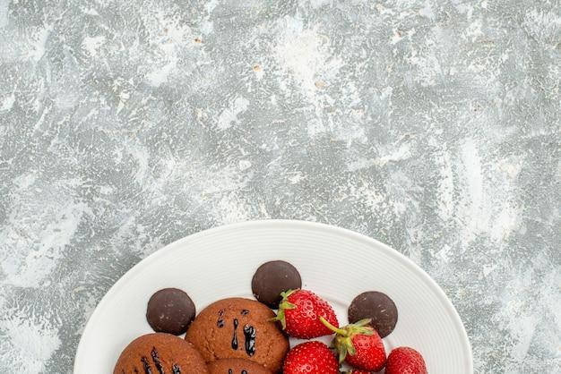 Schokoladenkekse erdbeeren und runde pralinen in der oberen hälfte auf dem weißen ovalen teller am unteren rand des grauweißen grundes