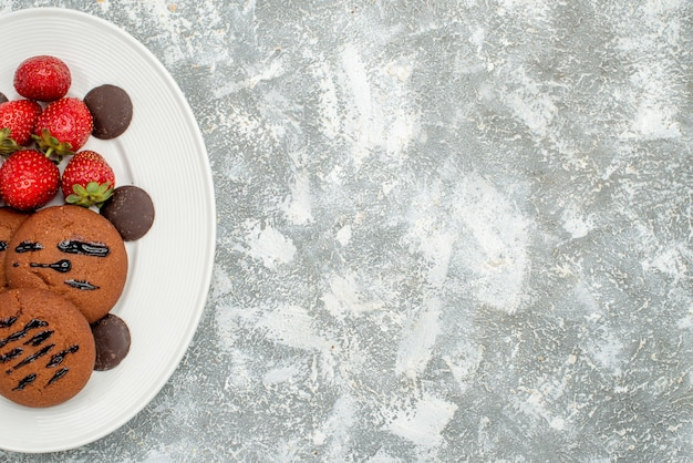 Schokoladenkekse erdbeeren und runde pralinen in der oberen hälfte auf dem weißen ovalen teller auf der linken seite des grauweißen grundes