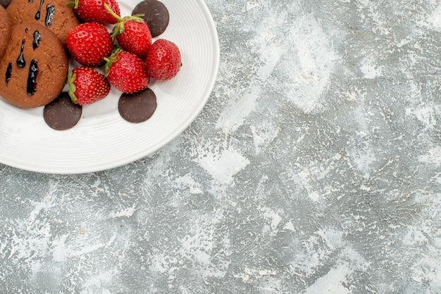 Schokoladenkekse erdbeeren und runde pralinen in der oberen hälfte auf dem weißen ovalen teller oben links auf dem grauweißen grund