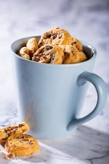 Schokoladenkekse in der blauen tasse auf marmorsteinoberfläche. selektiver fokus. speicherplatz kopieren