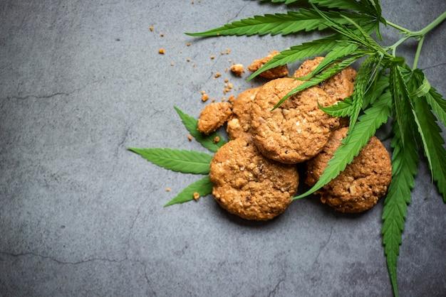 Schokoladenkekse mit cannabisblatt - marihuana-blätter-pflanze, cannabis-nahrung-natur-kräuter-konzept