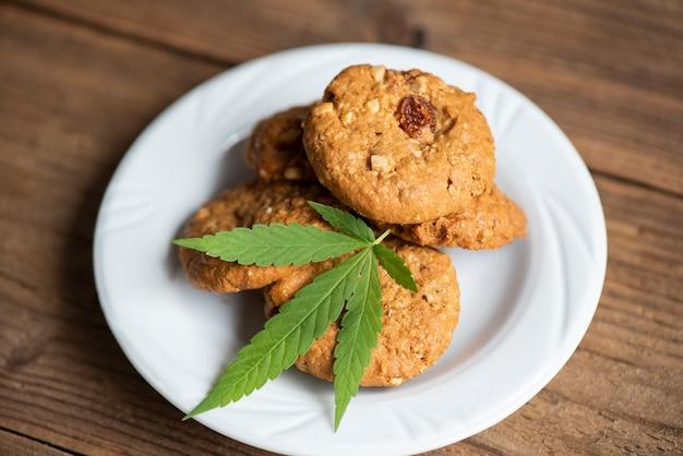 Schokoladenkekse mit cannabisblatt - marihuana-blätterpflanze auf weißem teller, cannabis-food-konzept