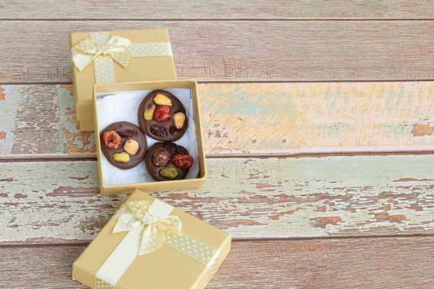 Schokoladenkekse mit nüssen in einer kleinen schachtel auf dem holztisch.