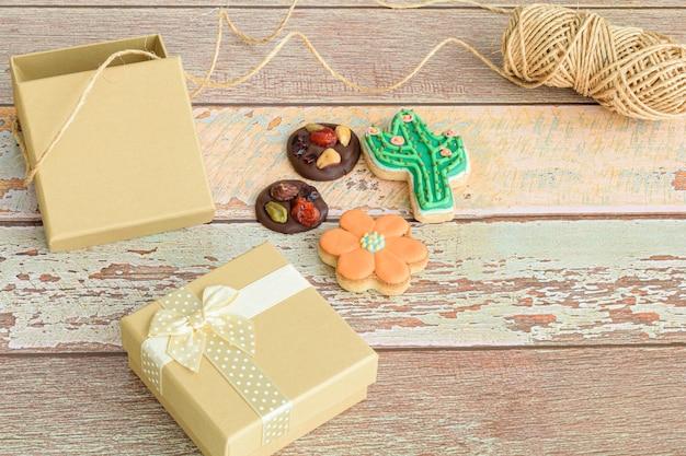 Schokoladenkekse mit nüssen und in form einer blume und eines kaktus, neben kleinen geschenkboxen und einer schnurrolle.