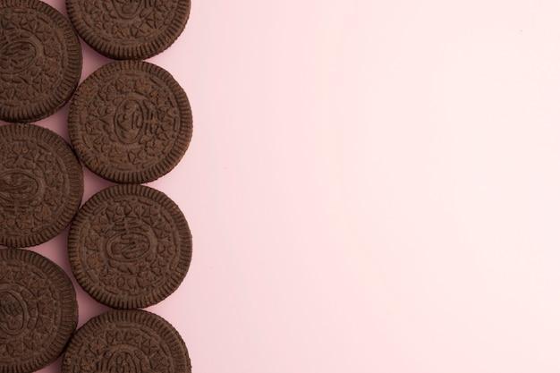 Schokoladenkekse mit sahne, die auf rosa hintergrund füllen. platz für text kopieren. flach legen