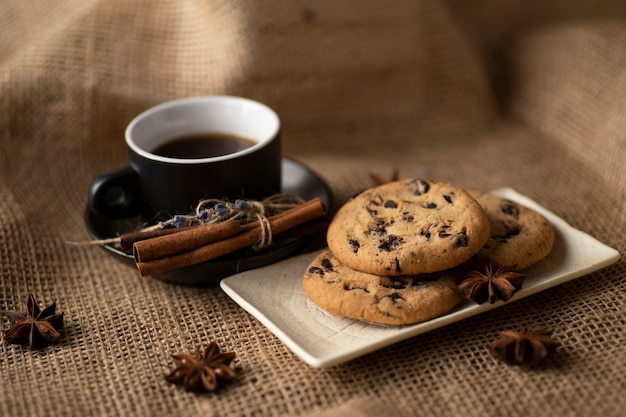 Schokoladenkekse und kaffee mit zimt auf einem tuch