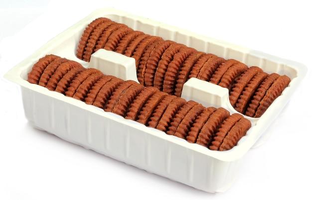 Schokoladenkekse und sahne auf weißem hintergrund