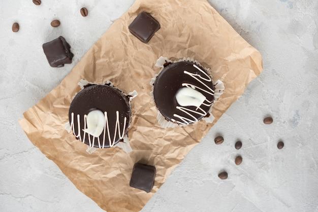 Schokoladenkleiner kuchen auf zerknittertem braunem papier mit kaffeebohnen