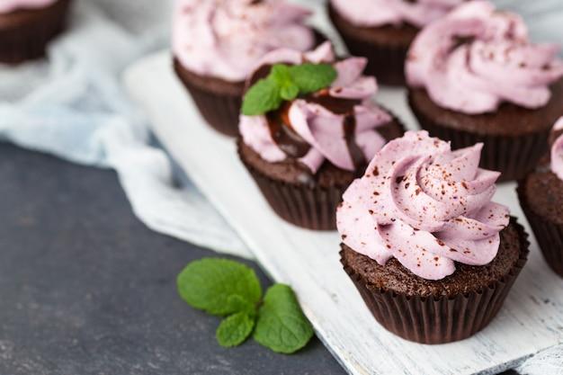 Schokoladenkleiner kuchen mit blaubeerkäsecreme auf einem weißen hölzernen brett