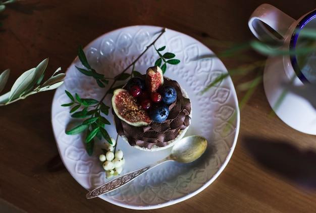 Schokoladenkleiner kuchen mit feigen und beeren auf einem holztisch. ansicht von oben