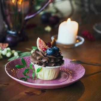 Schokoladenkleiner kuchen mit feigen und beeren auf festlicher tabelle