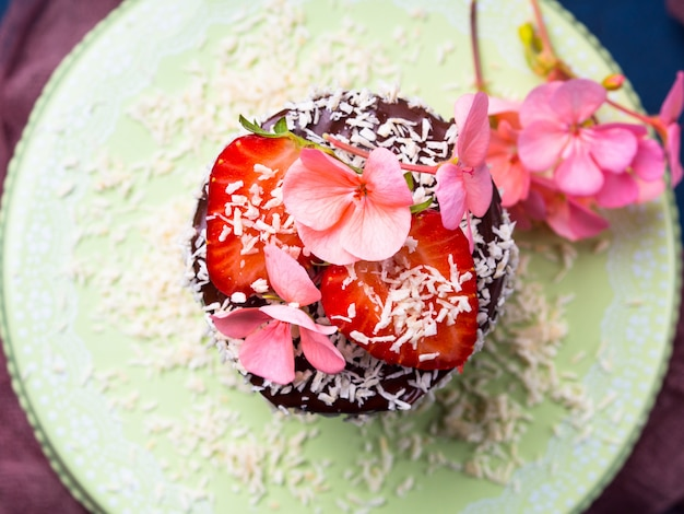 Schokoladenkokosnusskuchen mit erdbeerblumendekor auf dunkelblauem