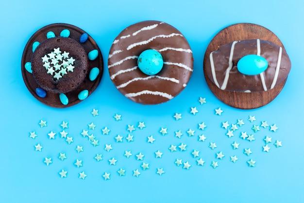 Schokoladenkrapfen der draufsicht mit blauen bonbons auf blauem schreibtisch, süße zuckerfarbe des bonbons