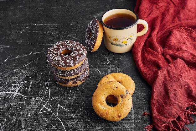 Schokoladenkrapfen und kekse mit einer tasse tee.