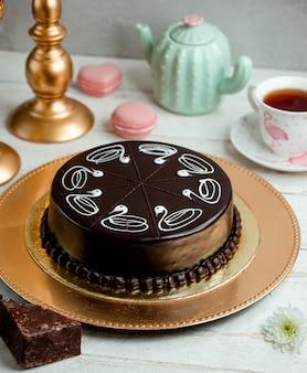 Schokoladenkuchen auf einem tablett und eine tasse duftenden tee