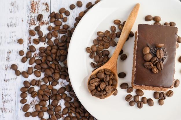Schokoladenkuchen auf einem weißen teller und kaffeebohnen auf einem holzlöffel auf einem holztisch.