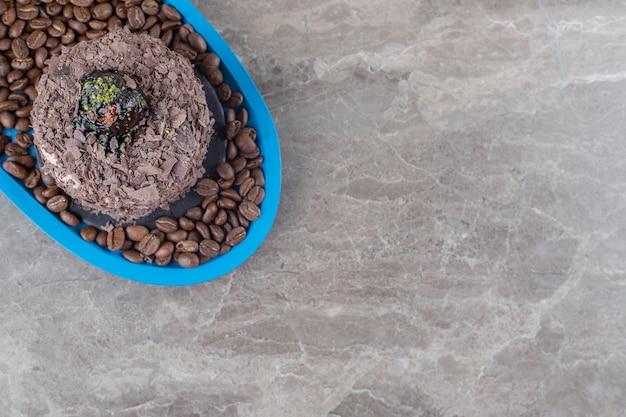Schokoladenkuchen auf einer platte voller kaffeebohnen auf marmoroberfläche