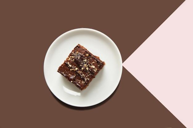 Schokoladenkuchen auf einer untertasse auf einem braunrosa geometrischen hintergrund ansicht von oben