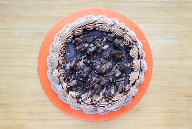 Schokoladenkuchen auf hölzernem bretthintergrund. draufsicht