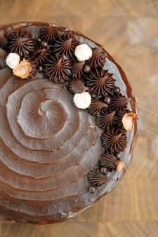 Schokoladenkuchen aus lockerem teig auf einem holztisch. geschnittener kuchen mit karamellfüllung.