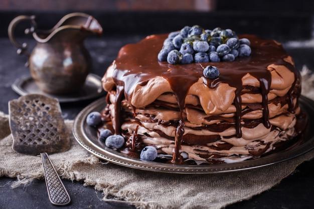 Schokoladenkuchen aus schokoladenpfannkuchen mit zuckerguss, mit blaubeeren.