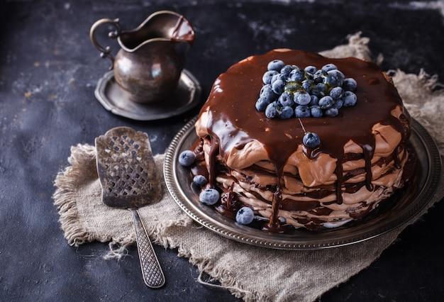 Schokoladenkuchen aus schokoladenpfannkuchen mit zuckerguss, mit blaubeeren