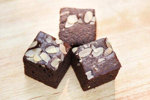 Schokoladenkuchen backen auf dem tisch - schokoladenkuchenscheibe mit nuss auf holz zusammen