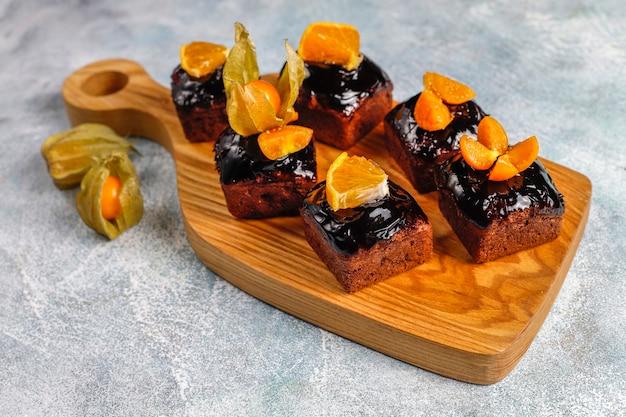 Schokoladenkuchen beißt mit schokoladensauce und mit früchten, beeren.