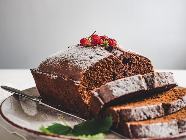 Schokoladenkuchen, frische beeren und weinleseteller