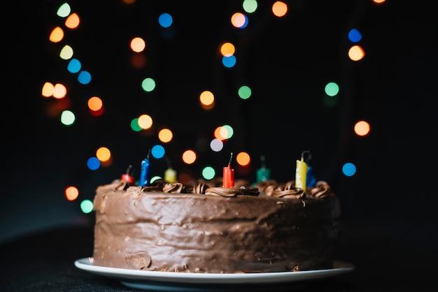 Schokoladenkuchen gegen das funkeln bokeh beleuchtet schwarzen hintergrund
