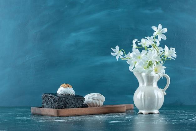 Schokoladenkuchen, keks und eine vase mit weißen lilien auf blau.