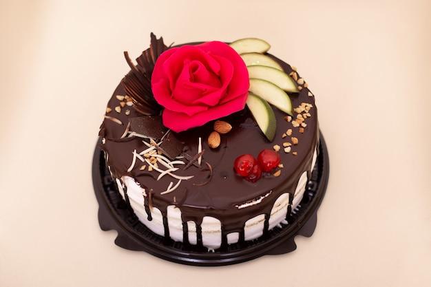 Schokoladenkuchen mit beerenfrüchten und nüssen verziert mit rosa rose