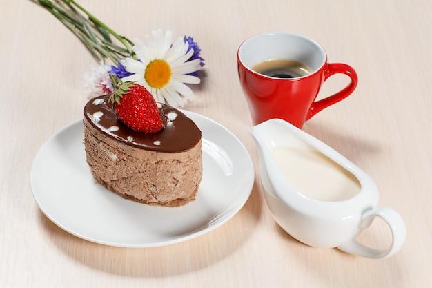 Schokoladenkuchen mit erdbeeren auf dem weißen teller, kamille und kornblumen, eine tasse kaffee und eine sauciere mit sahne auf einem holztisch