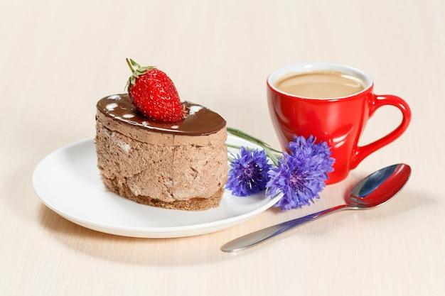 Schokoladenkuchen mit erdbeeren auf dem weißen teller, kornblumen und eine tasse kaffee auf einem holztisch