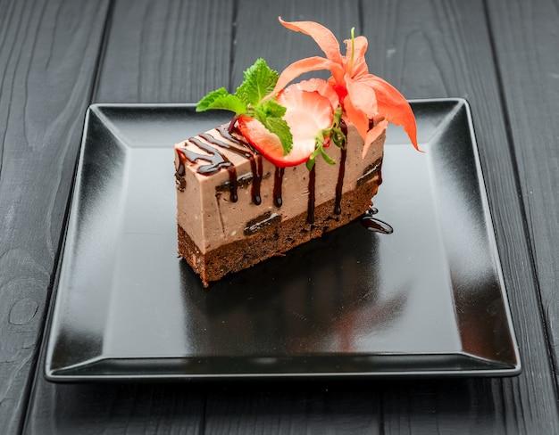 Schokoladenkuchen mit erdbeeren auf schwarzem teller und schwarz