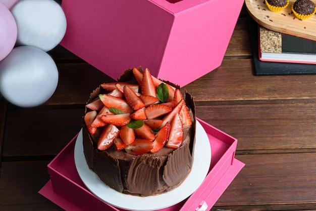 Schokoladenkuchen mit erdbeeren, basilikumblättern, brombeermarmelade und schokoladenplatten herum. neben ballons und brigadegeneral.