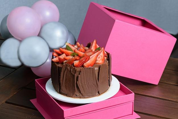 Schokoladenkuchen mit erdbeeren, basilikumblättern und schokoladenplatten herum, auf einer rosa schachtel. ballons im hintergrund.