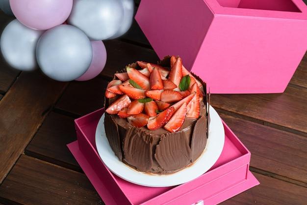 Schokoladenkuchen mit erdbeeren, basilikumblättern und schokoladenplatten herum, auf einer rosa schachtel (draufsicht). ballons im hintergrund.