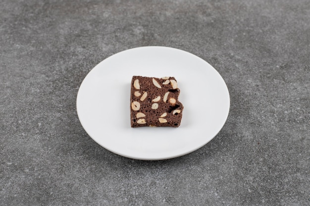 Schokoladenkuchen mit erdnuss. kuchenscheibe auf weißem teller über grauer oberfläche