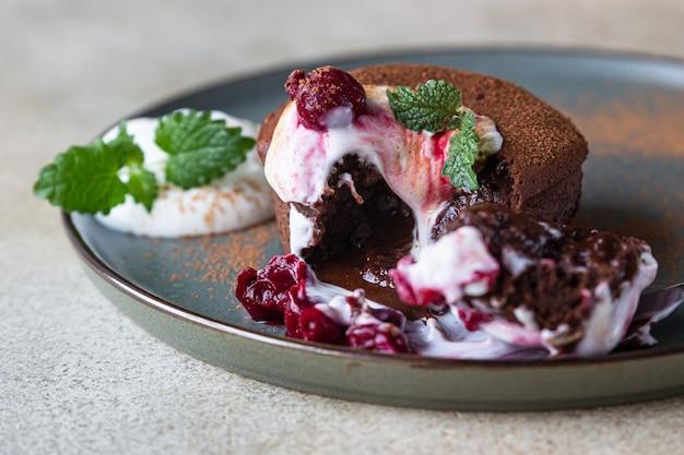 Schokoladenkuchen mit flüssiger füllung mit sahne, kirsche und minze. schokoladenfondue. schokoladen-lava-kuchen.