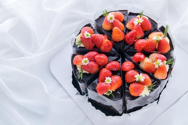 Schokoladenkuchen mit frischer erdbeere auf weißem stoff verziert