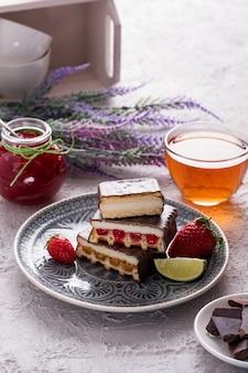Schokoladenkuchen mit früchten und tee zum frühstück.