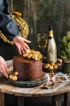 Schokoladenkuchen mit golddekor champagner hinter rustikaler frau übergibt hochwertiges foto
