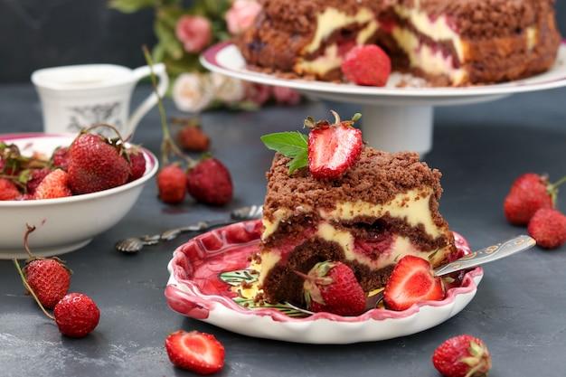 Schokoladenkuchen mit hüttenkäse mit erdbeeren befindet sich auf einem dunklen, ein stück kuchen befindet sich im vordergrund auf einem teller