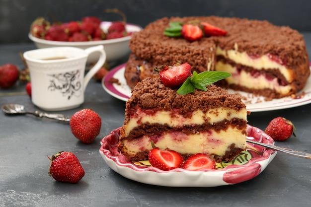 Schokoladenkuchen mit hüttenkäse mit erdbeeren befindet sich auf einer dunklen oberfläche, ein stück kuchen befindet sich im vordergrund auf einem teller